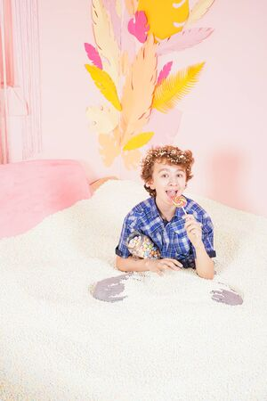 teen boy in the pool with foam soft small white balls. person engaged in relaxation therapy. caucasian kid with colorful lollipop on the stick on pink background. Zdjęcie Seryjne