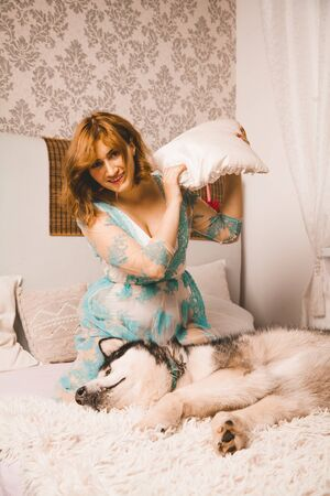 charming plus size girl with red hair in a nightgown posing with her large dog, a Malamute best friend in white bed in the bedroom Zdjęcie Seryjne - 133820597