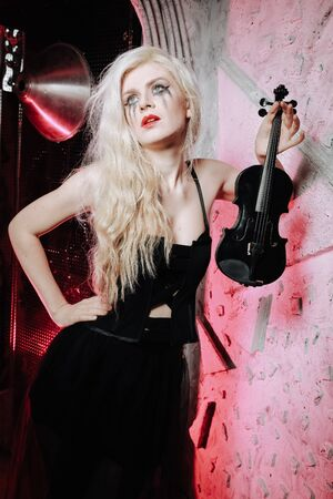 Blonde Gothic Girl with violin on white background. Young woman on the party.