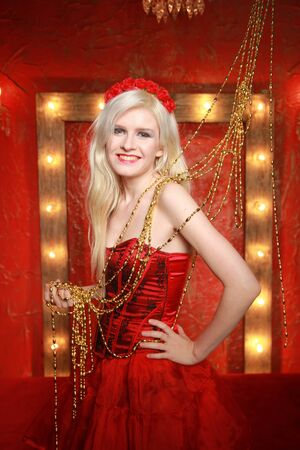 young fashion blonde lady posing in red corset dress on red fashion background with lamp bulbs frame with yellow warm light