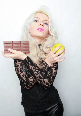 an attractive fit girl weighs her options of weather to eat chocolate or an apple. bad and good food.
