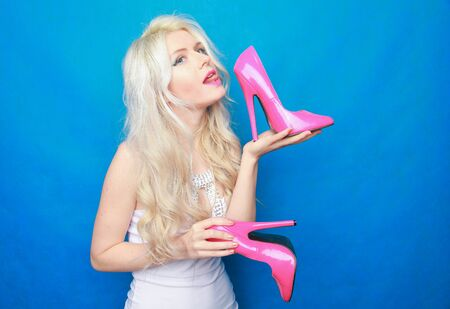 beautiful young model girl holds a lacquered hot pink Shoe and enjoys on a blue background in the Studio. high heels fetish concept. sales of footwear Reklamní fotografie