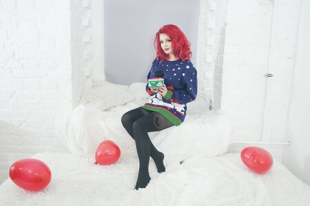 a beautiful girl in cozy warm clothes holds a large Cup of drink near the window sill at the window in her white room Stockfoto