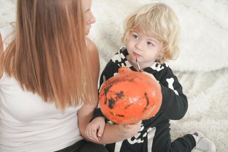 Young woman and her baby son have autumn fun with pumpkin on white windowsill, boy dressed in skeleton costume