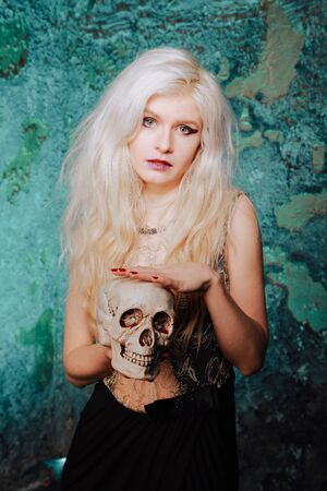 beautiful woman with blond hairstyle. adult slim girl with halloween skull in hands. mystic light. 免版税图像 - 133611964