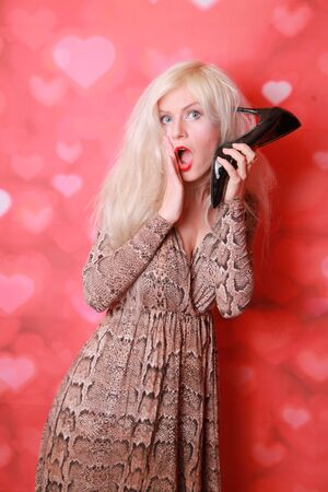 Young amazed woman using a shoe like a telephone holding it near her face and talking, red background. Pin-up style.