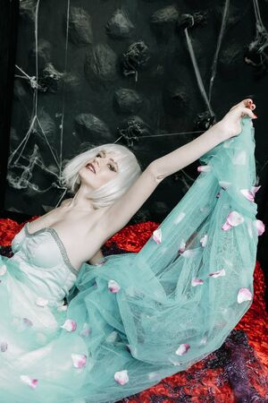 Young glamour girl doll in white wig and blue dress posing alone