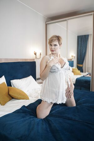 sexy blonde plus size short hair woman in lingerie transparent dress on bedroom background Banco de Imagens - 134104332