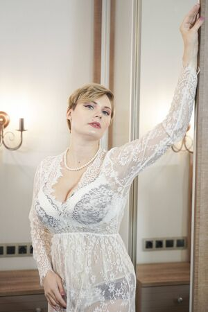 sexy blonde plus size short hair woman in lingerie transparent dress on bedroom background