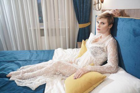 blonde plus size short hair woman in lingerie transparent dress on bedroom background