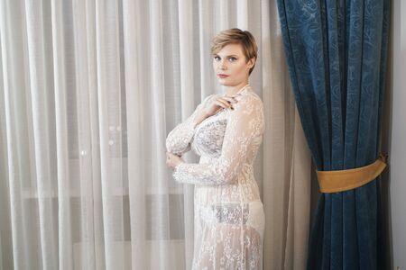 sexy blonde plus size short hair woman in lingerie transparent dress on bedroom background Banco de Imagens - 134104785