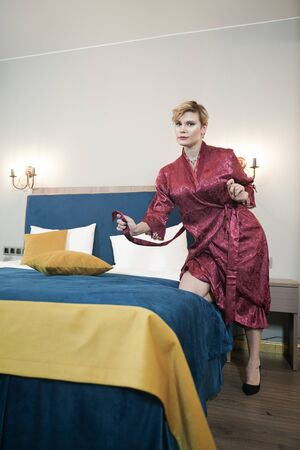 stylish pin up short hair blonde woman with plus size curvy body posing in fashion red bathrobe in the bedroom alone