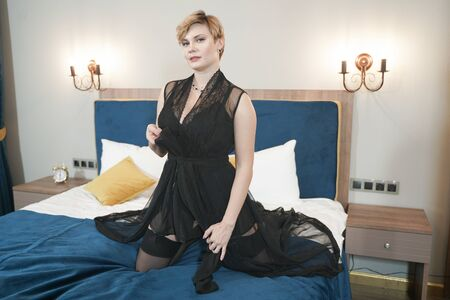 stylish pin up short hair blonde woman with plus size curvy body posing in fashion underwear in the bedroom alone