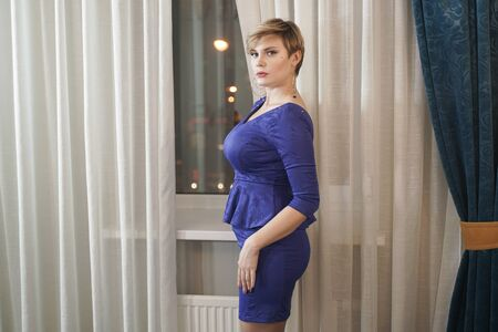 Beautiful blonde plus size young woman in blue dress standing by the window near white curtains