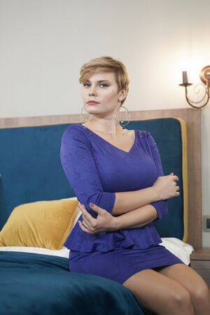 Young sexy curvy woman sitting in blue dress on the bed Zdjęcie Seryjne