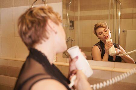 Photo of joyful female drying her hair after washing it in the bathroom near the mirror. Zdjęcie Seryjne