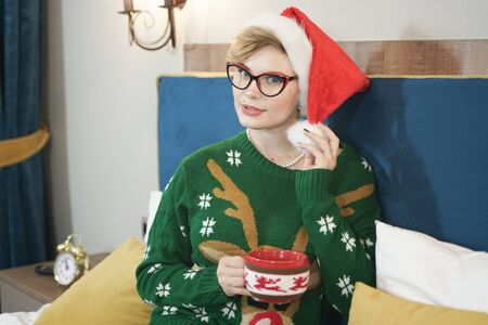 cute plus size nerd girl in glasses and green Christmas sweater with reindeer and red Santa Claus hat in the morning on the bed posing Zdjęcie Seryjne