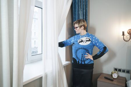 Fashion serious beautiful woman in blue christmas sweater looking through a window