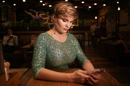 pretty woman with smart phone in the night cafe
