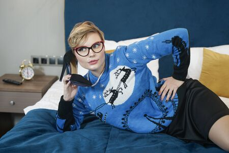 cute serious plus size short hair woman talking by shoe like a telephone lying on the bed in christmas blue sweater