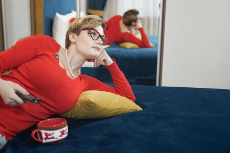 Young woman in red christmas sweater watching TV on the bed