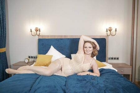 Voluptuous beautiful young curvy woman wearing retro beige lingerie with vintage stockings with seam. Adult sexy plus size girl in lingerie on the bed.