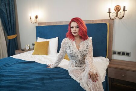 beautiful bride girl with red bob haircut in lace long dress posing in her bedroom alone