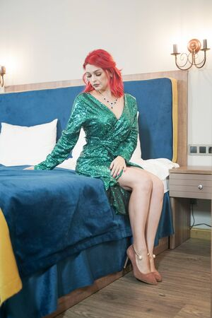 sexy woman in green stylish sparkling glitter dress ready for christmas party and relaz by waiting in her bed alone