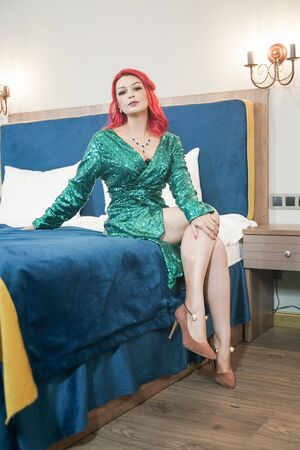 sexy woman in green stylish sparkling glitter dress ready for christmas party and relaz by waiting in her bed alone Stok Fotoğraf - 133960015