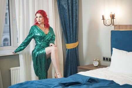 Cute bright red haired woman wearing green christmas glitter evening dress and standing near the window Stock Photo