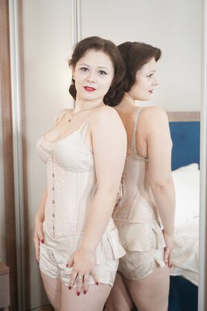 pretty pin up woman near the mirror standing in fashion lingerie
