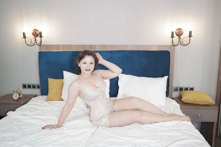 Retro fifties pin-up attractive girl in vintage lingerie on white bed background - pin-up concept