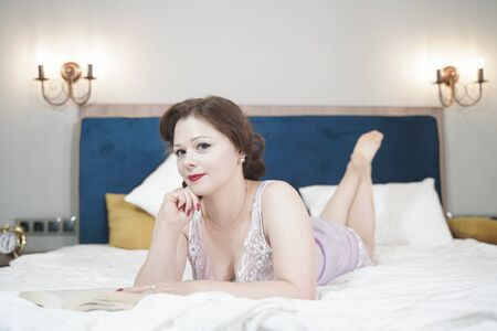 cute retro woman with book enjoy by reading and education on the bed. pretty girl in nightgown in the bedroom. Zdjęcie Seryjne