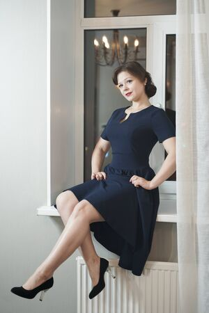 beautiful pin up woman in retro dress near a white window