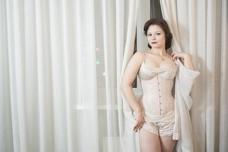 beautiful pinup girl in old fashionable lingerie and corset stands and holds the curtains, hiding behind them and playing