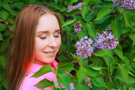 beautiful young teen girl standing in the flowers of lilac Banco de Imagens