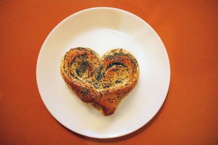 Valentine bun for breakfast for lovers on orange table background.