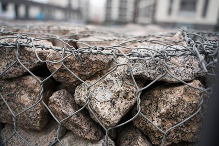 Detail shot of a stone retaining wall with stones in a steel cage