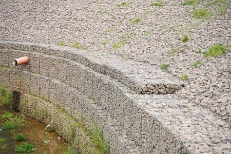 the edge of the city stream, made of stones in an iron grid