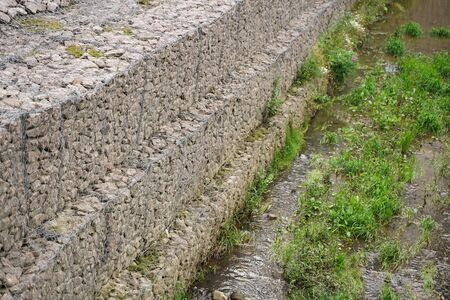 a newly made stream in the middle of the city in stone banks of small stones in an iron grid. the stream is dry, waiting for water to fill