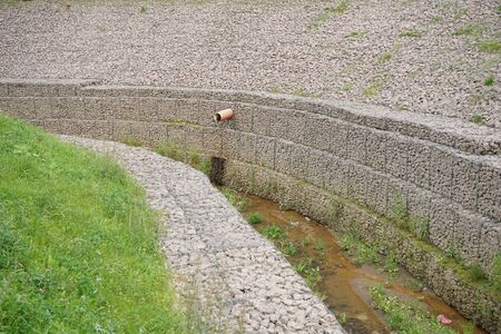 a newly made stream in the middle of the city in stone banks of small stones in an iron grid. the stream is dry, waiting for water to fill .