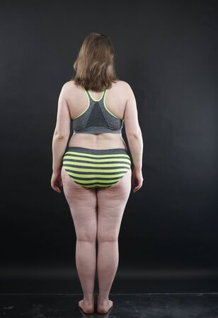 plus size woman shows her body in stretch marks and hair with cellulite and encourages you to love and accept yourself in any way . black background in the Studio. full length photo Zdjęcie Seryjne