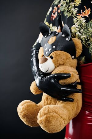 Bad Teddy Bear toy. woman in black latex gloves holds plush toy in leather mask and harness