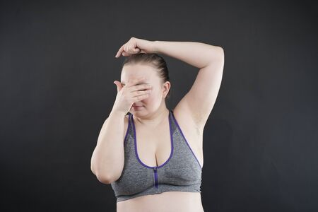 woman shows her unshaved armpit. plus size middle age woman is not happy with hair in her armpits. Caucasian girl is emotional sad and upset. black background in the photo Studio.