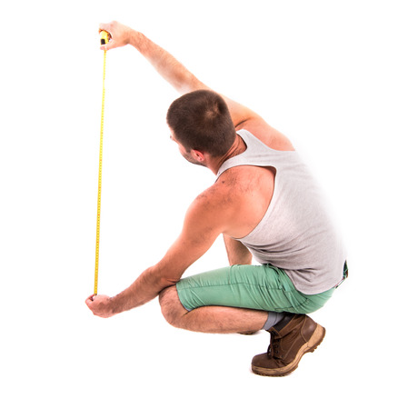 man measures the wall with a tape measure Stock Photo