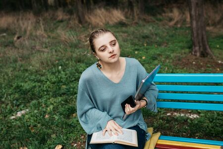 close up of woman sitting on colourful wooden bench in park. She is reading a book and holding laptop and mobile phone. Freelance work concept. Copy space for text. Zdjęcie Seryjne