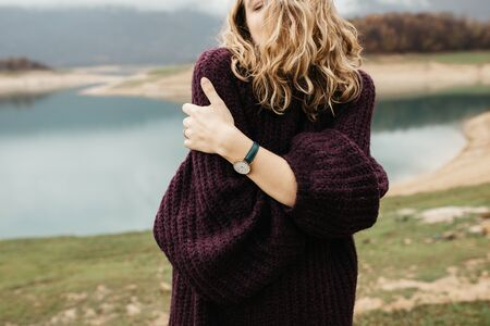 Close up photo of young female hands wearing fashionable wrist watch. She is standing near lake.