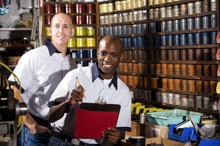 taking inventory: Two male multiracial workers in a printing shot