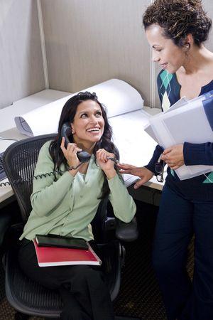 Zwei weibliche Spanier-Büroangestellte, die Sitzung am Kabine Schreibtisch Standard-Bild - 6170686