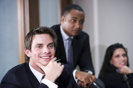 Young male businessman in boardroom meeting with multi-ethnic co-workers photo